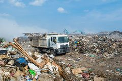 Lorry at the huge garbage dump full of smoke, litter, plastic bottles,rubbish and trash at the Thilafushi local tropical island Royalty Free Stock Photography