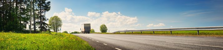 Lorry moving on sunny evening. Asphalt road on dandelion field with a small truck. lorry moving on sunny evening Stock Images