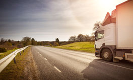 Lorry moving on sunny evening. Asphalt road on dandelion field with a small truck. lorry moving on sunny evening royalty free stock photo