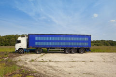 Lorry park. An articulated lorry with white cab and blue curtain sided trailer parked in a rural sitting with trees and a blue sky background and lots of stock image
