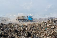 Lorry riding at the garbage dump full of smoke, litter, plastic bottles,rubbish and trash at tropical island. Lorry riding at the huge garbage dump full of smoke Royalty Free Stock Photo