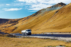 Lorry on a road through mountains Stock Photo