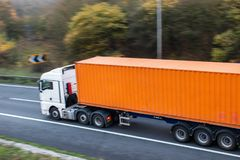 Lorry with shipping container on the road. Lorry with orange shipping container in motion on the road stock photos