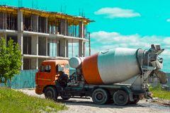 A lorry is a truck with a cab of orange color on a construction site of a high-rise house under construction in the city. Back view, Surgut, Russia - June 20 stock image