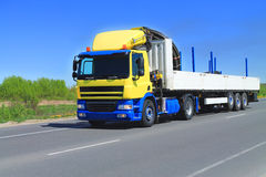 Lorry truck with flatbed semitrailer. Yellow-blue lorry truck with white flatbed semitrailer moving over blue sky on the road Royalty Free Stock Photos