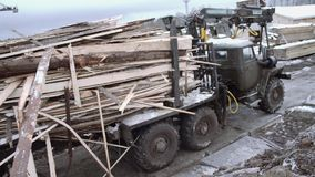 Lorry truck riding on dirty road at woodwork production yard. Lorry green metal truck full of wood riding on dirty road at woodwork production yard, winter stock video footage