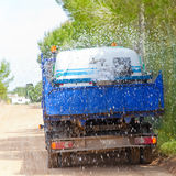 Lorry truck spreading sprinkle water on sand road Stock Images