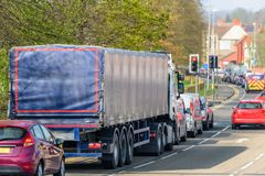Lorry truck stuck in busy traffic on road in british town at noon time stock photos