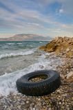 Lorry tyre on sea shore - Pollution Stock Images