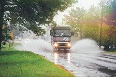 Lorry on wet road rides through a puddle. Lorry on wet road was in a deep puddle and created a large flow of water that has become an obstacle to the flow of Royalty Free Stock Photo