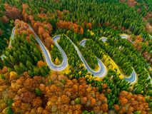 Aerial view of winding road through autumn colored forest. Lorry winding up its way on a curvy road through autumn colored forest Stock Photos