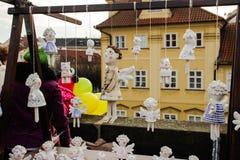 Los ángeles de cerámica con las alas cuelgan en las cuerdas en el mercado de la Navidad foto de archivo