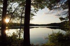 Los árboles abrazan una puesta del sol que pasa por alto un lago vidrioso fotos de archivo libres de regalías