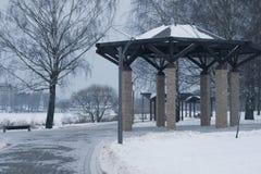 Los árboles y los bancos nevados en la ciudad parquean fotos de archivo libres de regalías