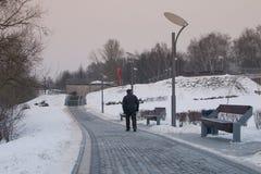 Los árboles y los bancos nevados en la ciudad parquean Un hombre mayor en un parque de la reconstrucción imagen de archivo libre de regalías