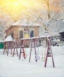 Los árboles y los oscilaciones nevados en la ciudad parquean Fotografía de archivo libre de regalías