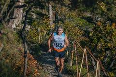 Los últimos años masculinos del atleta corren en un rastro de montaña Imágenes de archivo libres de regalías