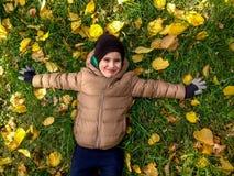 Los 4 años alegres del muchacho que miente en amarillo se van en otoño Visión superior Foto de archivo