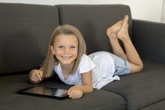 Los años dulces y felices jovenes de la niña 6 o 7 que mienten en el sofá casero de la sala de estar acuestan con la almohadilla  Imagenes de archivo