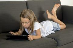 Los años dulces y felices jovenes de la niña 6 o 7 que mienten en el sofá casero de la sala de estar acuestan con la almohadilla  Fotos de archivo libres de regalías