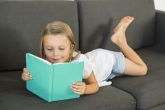 Los años dulces y felices jovenes de la niña 6 o 7 que mienten en el sofá casero de la sala de estar acuestan leyendo una tranqui Imagen de archivo libre de regalías