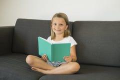 Los años dulces y felices jovenes de la niña 6 o 7 que se sientan en el sofá casero de la sala de estar acuestan leyendo una tran Imagenes de archivo