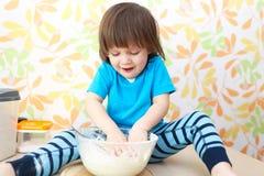 Los 2 años felices de muchacho cocinan sentarse en una cocina de la tabla en casa Imagen de archivo