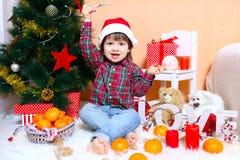 Los 2 años felices de muchacho en el sombrero de Papá Noel se sientan cerca del árbol de navidad Fotos de archivo libres de regalías