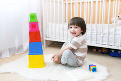 Los 2 años felices de muchacho juegan el juguete educativo en casa Imagen de archivo libre de regalías