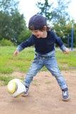 Los 2 años felices de muchacho juegan a fútbol al aire libre Imagen de archivo