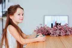 los 5 años felices embroman a la muchacha que desayuna en casa en la mañana Foto de archivo libre de regalías