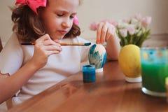 Los 7 años felices embroman a la muchacha que pinta los huevos de Pascua Preparaciones del arte y del día de fiesta de Pascua Fotografía de archivo libre de regalías