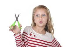Los años femeninos hermosos dulces del niño 6 a 8 que llevan a cabo el corte scissors concepto de las fuentes de escuela imagen de archivo