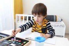 Los 3 años lindos de muchacho están pintando con la acuarela Imagen de archivo libre de regalías