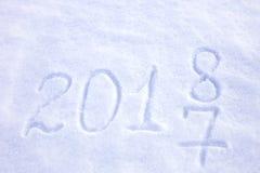 los Años Nuevos fechan 2018 escrito en fondo de la nieve Imagen de archivo libre de regalías