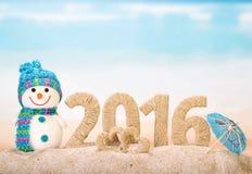 Los Años Nuevos firman con el muñeco de nieve en la playa del mar Imagen de archivo libre de regalías