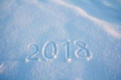Los Años Nuevos firman 2018, manuscrito en la nieve fresca, tarjeta de felicitación de Fotografía de archivo libre de regalías