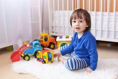 Los 2 años preciosos de muchacho juegan los coches en casa Foto de archivo libre de regalías