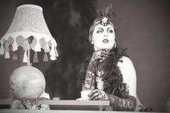 Los años 20 retros de la mujer - los años 30 que se sientan con adentro un restaurante que sostiene a Imagenes de archivo
