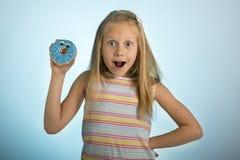 Los años rubios felices y emocionados hermosos jovenes de la muchacha 8 o 9 que sostienen el buñuelo abandonan en su mano que par Foto de archivo