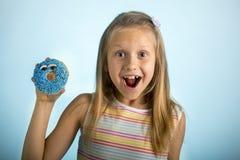 Los años rubios felices y emocionados hermosos jovenes de la muchacha 8 o 9 que sostienen el buñuelo abandonan en su mano que par Imagen de archivo libre de regalías