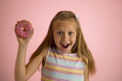 Los años rubios felices y emocionados hermosos jovenes de la muchacha 8 o 9 que sostienen el buñuelo abandonan en su mano que par Fotos de archivo