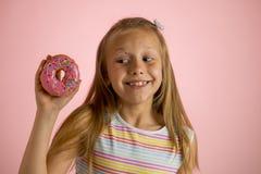 Los años rubios felices y emocionados hermosos jovenes de la muchacha 8 o 9 que sostienen el buñuelo abandonan en su mano que par Fotografía de archivo