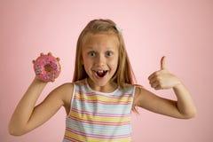 Los años rubios felices y emocionados hermosos jovenes de la muchacha 8 o 9 que sostienen el buñuelo abandonan en su mano que par Fotografía de archivo libre de regalías