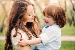 los abrazos de la mamá y el niño felices del beso embroman al hijo al aire libre en primavera o verano imagen de archivo libre de regalías