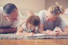 Los abuelos ayudan a su nieta a escribir a casa fotografía de archivo libre de regalías