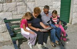 Los abuelos con los nietos miran una foto fotos de archivo
