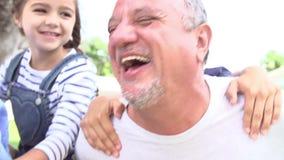 Los abuelos que dan a nietos llevan a cuestas paseo en jardín almacen de video