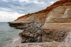 Los acantilados que erosionan en el puerto Noarlunga y las rocas protectoras pl foto de archivo libre de regalías