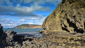 Los acantilados y las formaciones de roca a lo largo de la arena negra Whatipu varan en Huia Fotos de archivo